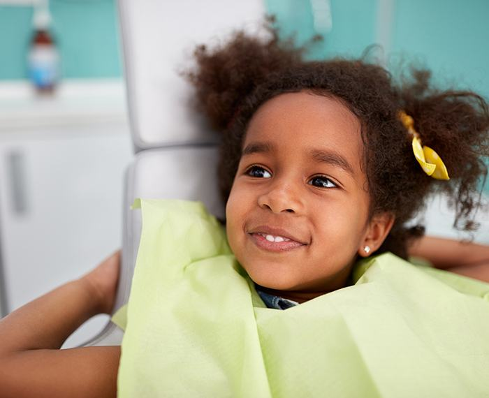 Little girl in dental chair smiling during children's dentistry visit